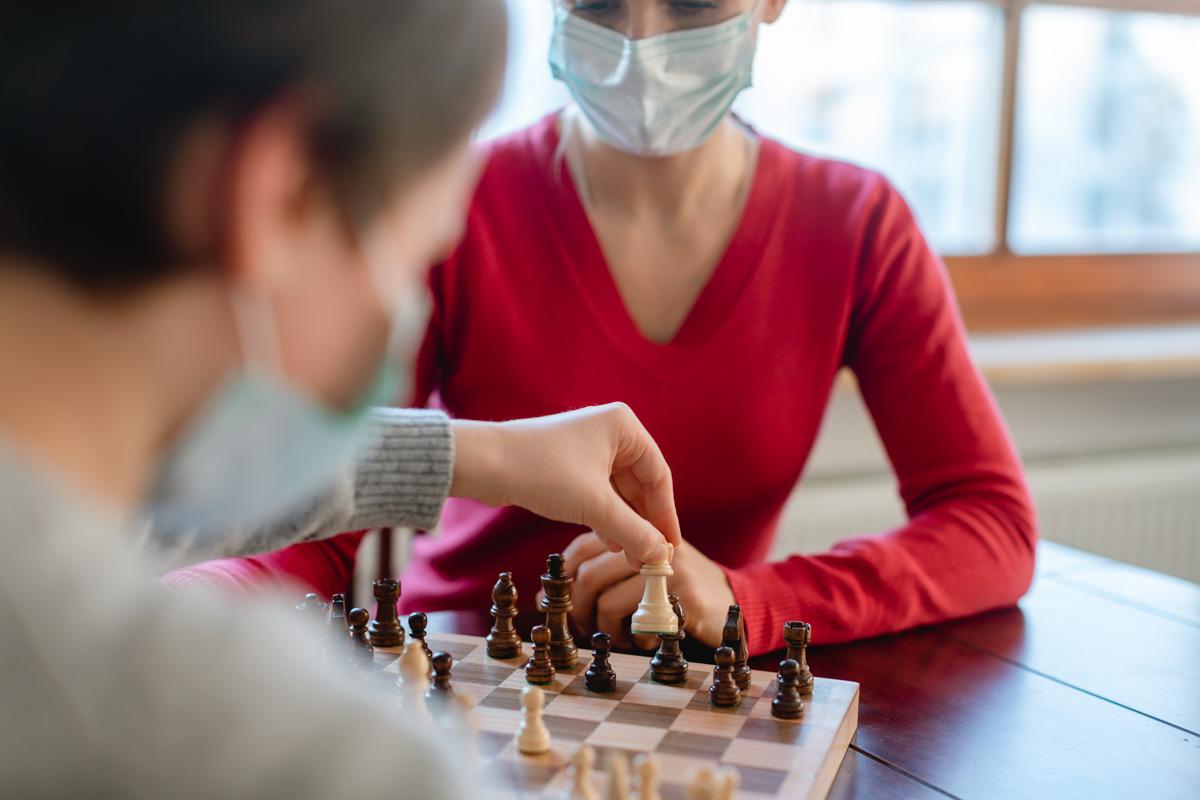 Famile trägt Masken in der Covid-19 Krise und spielt daheim Schach